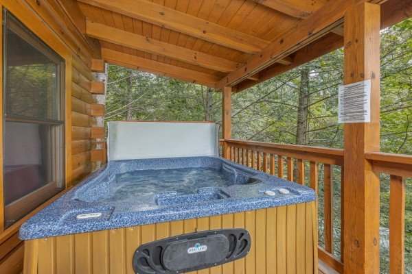 Hot tub on a covered deck at Cub's Crossing, a 3 bedroom cabin rental located in Gatlinburg