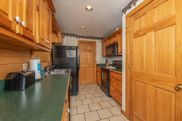 Galley kitchen with black appliances at Cub's Crossing, a 3 bedroom cabin rental located in Gatlinburg
