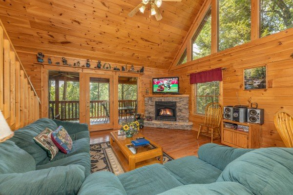 Living room with sofa, loveseat, fireplace, and TV at Cub's Crossing, a 3 bedroom cabin rental located in Gatlinburg