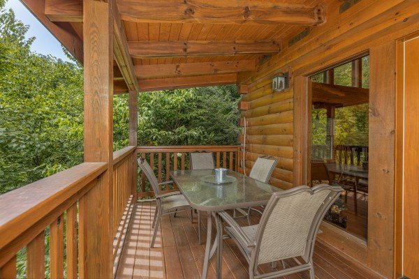 Outdoor dining for four on a covered deck at Cub's Crossing, a 3 bedroom cabin rental located in Gatlinburg