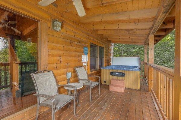Two chairs, a table, and a hot tub on a covered deck at Cub's Crossing, a 3 bedroom cabin rental located in Gatlinburg