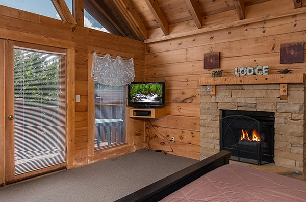 Bedroom with a TV, fireplace, and deck access at Little Moon, a 1 bedroom cabin rental located in Pigeon Forge