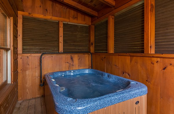Hot tub on a covered deck with privacy fencing at Little Moon, a 1 bedroom cabin rental located in Pigeon Forge