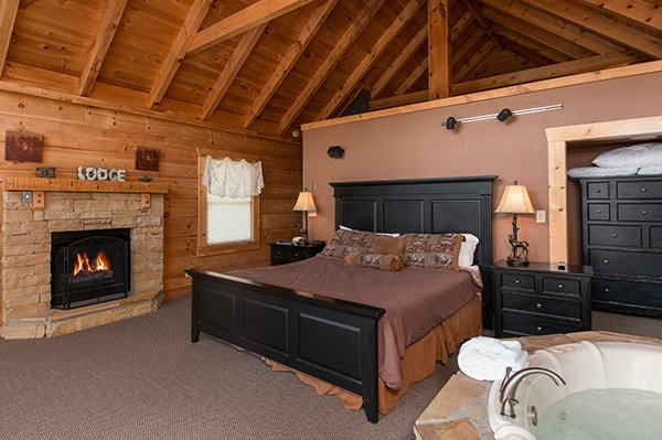 Bedroom with a king bed, fireplace, and in room jacuzzi at Little Moon, a 1 bedroom cabin rental located in Pigeon Forge