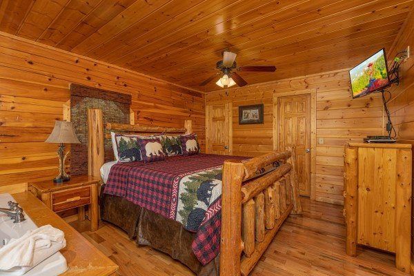 Bedroom with a king bed, night stand, lamp, TV, and dresser at Bear O'clock Somewhere, a 5 bedroom cabin rental located in Pigeon Forge