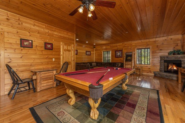 Pool table, arcade game, and fireplace in a game room at Bear O'clock Somewhere, a 5 bedroom cabin rental located in Pigeon Forge