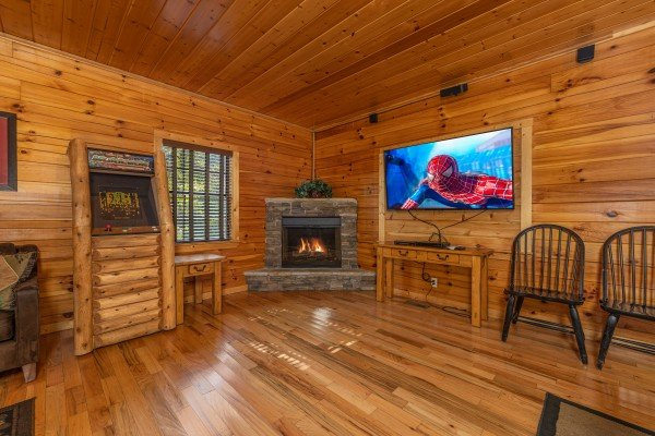 Fireplace and large TV in the game room at Bear O'clock Somewhere, a 5 bedroom cabin rental located in Pigeon Forge