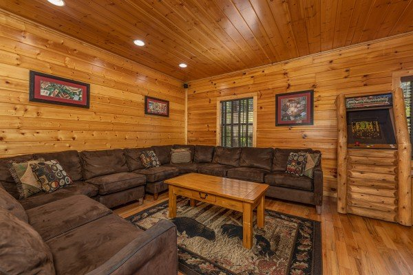 Large sectional sofa and arcade game at Bear O'clock Somewhere, a 5 bedroom cabin rental located in Pigeon Forge