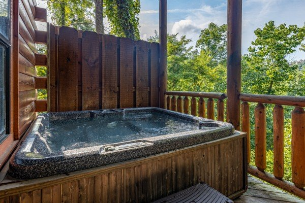 Hot tub with privacy fence at Bear O'clock Somewhere, a 5 bedroom cabin rental located in Pigeon Forge