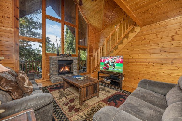Living room with large windows, fireplace, and TV at Bear O'clock Somewhere, a 5 bedroom cabin rental located in Pigeon Forge