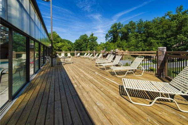 Sundeck at the pool for guests at Bear O'clock Somewhere, a 5 bedroom cabin rental located in Pigeon Forge