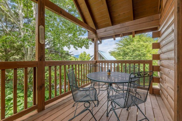 Deck dining for four at Logged Inn, a 3 bedroom cabin rental located in Pigeon Forge