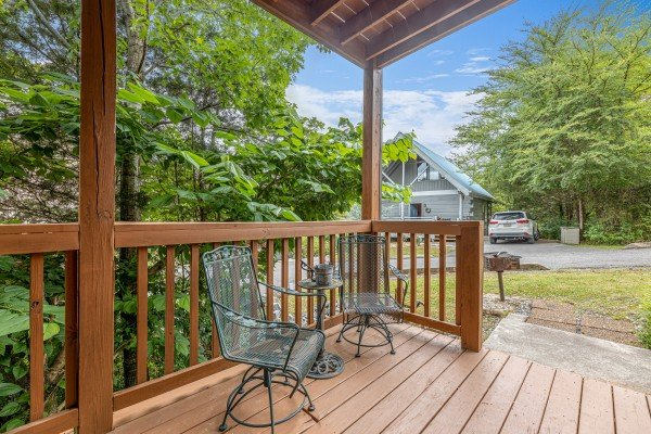 Chair and table on a covered deck at Logged Inn, a 3 bedroom cabin rental located in Pigeon Forge