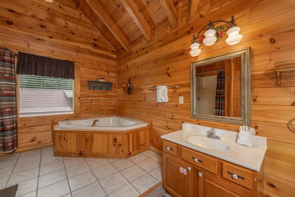 Corner jacuzzi tub in an en suite bath at Logged Inn, a 3 bedroom cabin rental located in Pigeon Forge