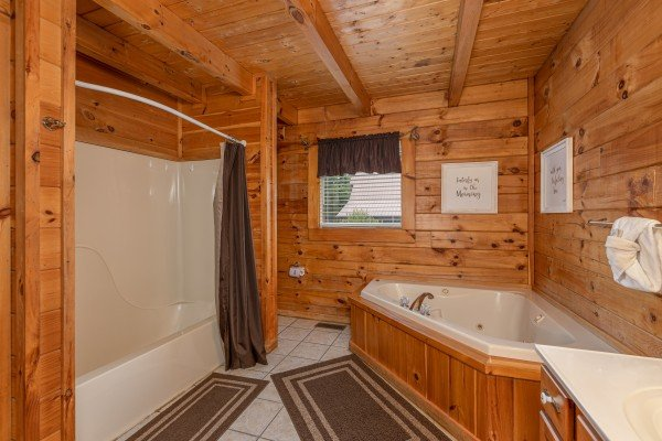 Bathroom with a tub, shower, and jacuzzi at Logged Inn, a 3 bedroom cabin rental located in Pigeon Forge