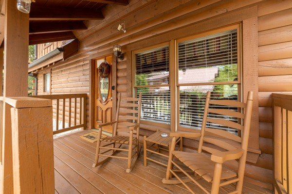 Rocking chairs on a covered front porch at Logged Inn, a 3 bedroom cabin rental located in Pigeon Forge