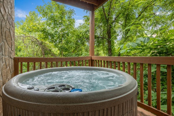 Hot tub on a covered deck at Logged Inn, a 3 bedroom cabin rental located in Pigeon Forge