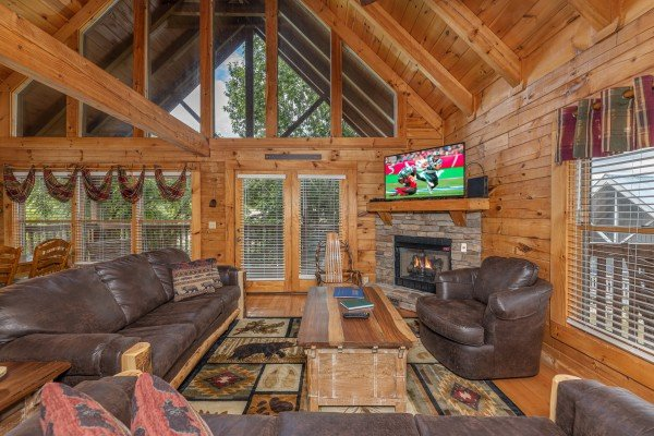 Living room with fireplace, TV, seating, and large windows at Logged Inn, a 3 bedroom cabin rental located in Pigeon Forge