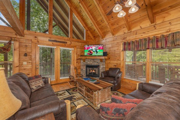 Fireplace, TV, and seating in a living room at Logged Inn, a 3 bedroom cabin rental located in Pigeon Forge