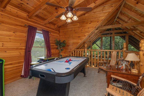 Loft with an air hockey table at Logged Inn, a 3 bedroom cabin rental located in Pigeon Forge