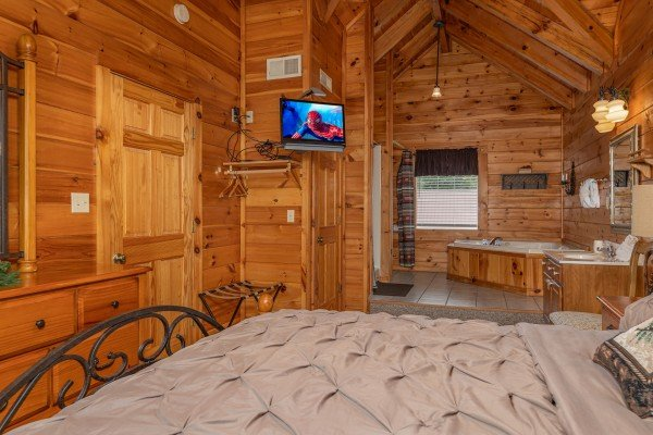 Dresser, TV, and en suite open bath with jacuzzi at Logged Inn, a 3 bedroom cabin rental located in Pigeon Forge