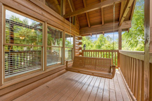 Swing on a covered deck at Logged Inn, a 3 bedroom cabin rental located in Pigeon Forge