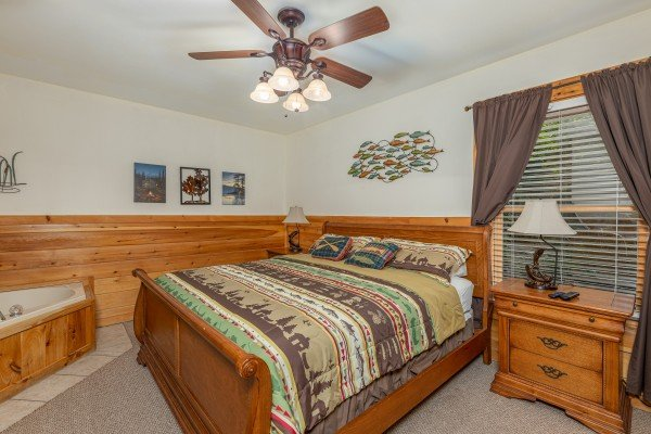 Bedroom with sleigh bed, night stands, and lamps at Logged Inn, a 3 bedroom cabin rental located in Pigeon Forge