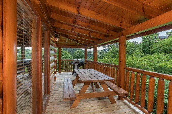 Picnic table and propane grill on the covered deck at Happy Daze, a 2-bedroom Pigeon Forge cabin rental