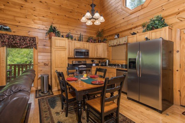Kitchen with stainless appliances and dining table at Happy Daze, a 2-bedroom Pigeon Forge cabin rental