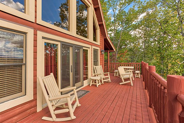 Open deck with rocking chairs and bench seating at Mountain Wonderland, a 3 bedroom cabin rental located in Pigeon Forge