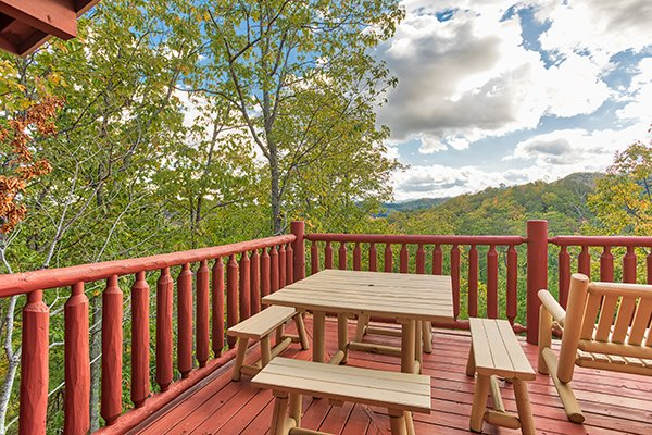 Dining table for four on the deck at Mountain Wonderland, a 3 bedroom cabin rental located in Pigeon Forge