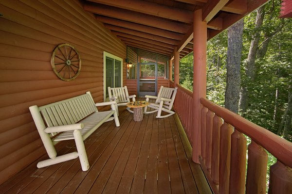 Bench and rocking chairs on the covered deck at Mountain Wonderland, a 3 bedroom cabin rental located in Pigeon Forge