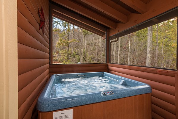 Hot tub on a covered, screened deck at Mountain Wonderland, a 3 bedroom cabin rental located in Pigeon Forge