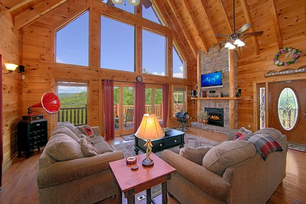 Living room with tall windows, fireplace, and TV at Mountain Wonderland, a 3 bedroom cabin rental located in Pigeon Forge