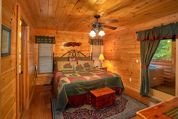 King sized bed in a bedroom with deck access at Mountain Wonderland, a 3 bedroom cabin rental located in Pigeon Forge