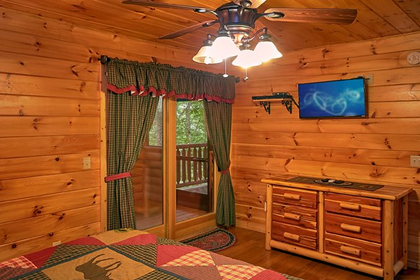Bedroom with deck access, dresser, and TV at Mountain Wonderland, a 3 bedroom cabin rental located in Pigeon Forge