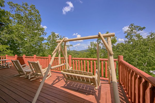 Porch swing and rocking chairs at Mountain Wonderland, a 3 bedroom cabin rental located in Pigeon Forge