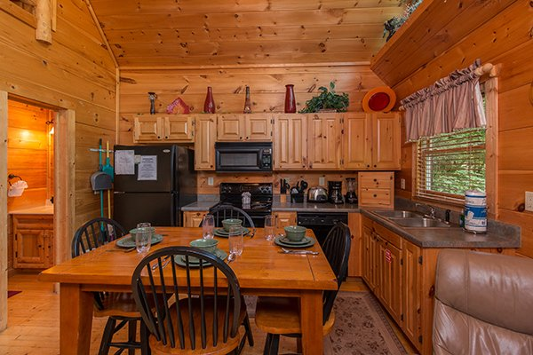 Dining space for four in a kitchen with black appliances at True Love, a 1 bedroom cabin rental located in Gatlinburg
