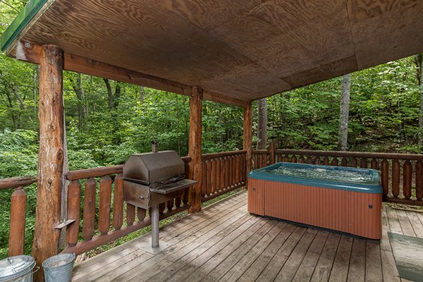 Grill and hot tub on a covered deck at True Love, a 1 bedroom cabin rental located in Gatlinburg