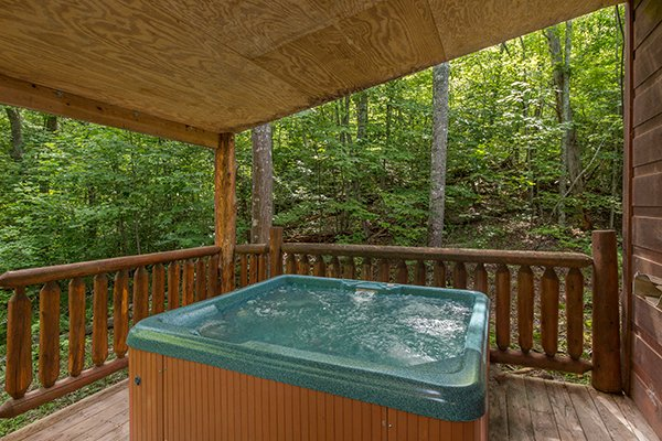 Hot tub on a covered deck surrounded by woods at True Love, a 1 bedroom cabin rental located in Gatlinburg