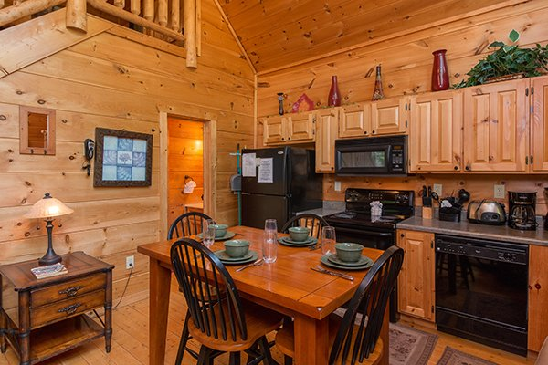 Dining space for four in the kitchen with black appliances at True Love, a 1 bedroom cabin rental located in Gatlinburg