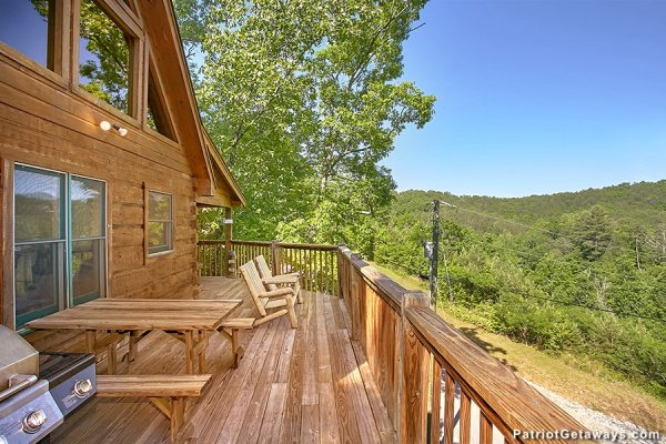 Deck with grill, picnic table, and Adirondack chairs at Picture Perfect Hideaway, a 2 bedroom cabin rental located in Pigeon Forge