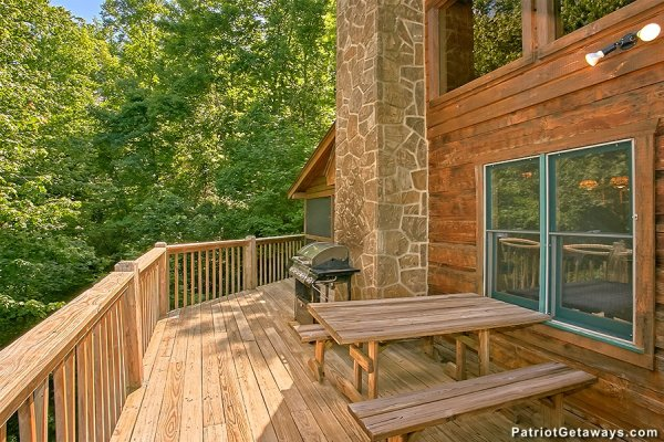 Picnic table and grill on the deck at Picture Perfect Hideaway, a 2 bedroom cabin rental located in Pigeon Forge