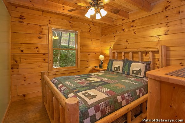 Queen log bed in a bedroom at Picture Perfect Hideaway, a 2 bedroom cabin rental located in Pigeon Forge