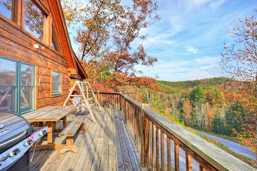 Deck with grill, picnic table, and swing at Picture Perfect Hideaway, a 2 bedroom cabin rental located in Pigeon Forge