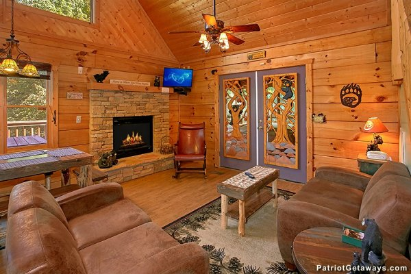 Vaulted living room with fireplace and TV at Picture Perfect Hideaway, a 2 bedroom cabin rental located in Pigeon Forge