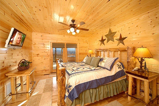 king sized log framed bed on first floor of elk ridge lodge a 4 bedroom cabin rental located in gatlinburg