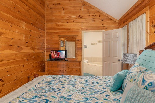Dresser, TV, and en suite bath at Bear it All, a 2 bedroom cabin rental located in Sevierville