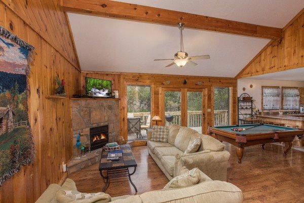 Living room with vaulted ceiling, fireplace, television, and pool table at Bear it All, a 2-bedroom cabin rental located in Sevierville