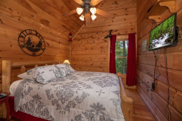 Bedroom with a king bed and TV at Logan's Smoky Den, a 2 bedroom cabin rental located in Pigeon Forge